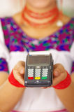 Closeup credit card terminal, woman wearing traditional andean indigenous clothing holding device in front of camera Royalty Free Stock Photos