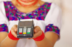 Closeup credit card terminal, woman wearing traditional andean indigenous clothing holding device in front of camera Royalty Free Stock Photo