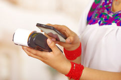 Closeup credit card terminal, woman wearing traditional andean indigenous clothing holding mobile and payment device in Royalty Free Stock Photos
