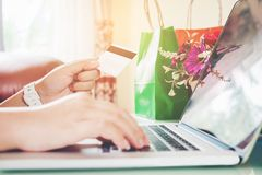 Closeup credit card ,Woman shopping online using laptop with credit card enjoying in home Stock Photos