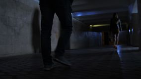 Closeup criminal`s legs chasing victim in darkness