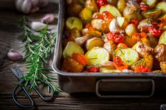Closeup of crispy roasted potato with tomatoes and garlic Royalty Free Stock Photo