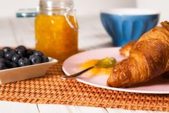 Closeup of croissant and blueberries over a tablecloth Royalty Free Stock Image