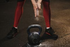 Closeup of crossfit female athlete claping hands and getting ready for kettlebell workout royalty free stock images