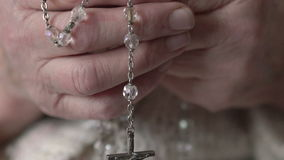 Closeup crucifix, crystal rosary in old hands stock footage