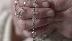 Closeup crucifix and crystal rosary in old hands. Slow motion stock video