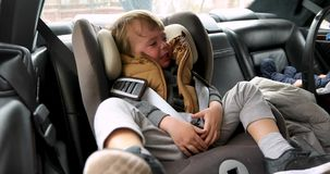 Closeup crying boy with worried stressed expression. In child safety seat in car interior stock video footage