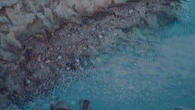 Clean transparent ocean water. Closeup of crystal clear blue lagoon ocean water near rocks stock video