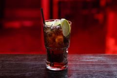 Closeup of a Cuba Libre cocktail in short glass, gin, standing on the bar counter, isolated on a red background. royalty free stock photo