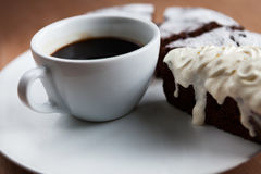 Closeup of cup of black coffee and cake with cream Royalty Free Stock Images