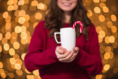 Closeup of cup with candy cane holded by smiling female Stock Photography