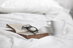 Closeup of a cup of coffe, old book and rimmed glasses on a white pillow. Stock Photos