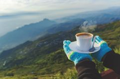 Closeup a cup of coffee in traveler`s hand over out of focus mountains view stock photography