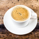 Closeup cup of espresso on old wooden table over grunge backgrou Royalty Free Stock Image