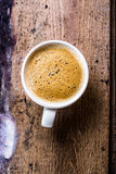 Closeup cup of espresso on old wooden table over grunge background, top view royalty free stock images