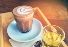Closeup cup of hot chocolate art on saucer with spoon and tea. Stock Photography