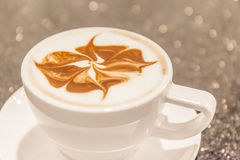 Closeup cup of hot coffee with art foam milk decoration. Royalty Free Stock Image