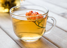 Closeup of cup of tea with bright flower on wooden table with teapot on background. still life with tea cup. Royalty Free Stock Photos