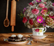 Closeup of cup of tea with cake and flowers bouquet on the wood table close up photo Stock Images