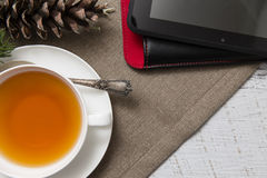 Closeup of cup of tea with Christmas decoration and tablet noteb Royalty Free Stock Images