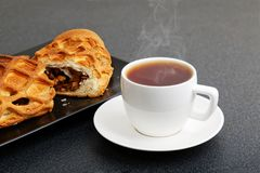 Closeup cup of tea and strudel with apples and cinnamon Stock Photography