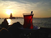 Closeup of a cup of Turkish tea in front of Maiden`s Tower stock photography