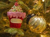 Closeup Cupcake and ball ornament on Christmas tree. royalty free stock image
