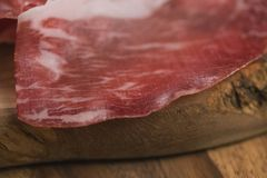 Closeup cured italian coppa on olive wood board. Shallow focus Royalty Free Stock Images