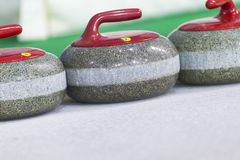 Closeup of Curling Blue Handle Stones on Ice.With Copyspace Stock Images
