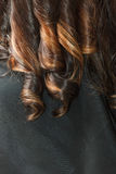Closeup of curly dark woman hair. Hairstyling and haircare concept. Closeup of healthy curly dark brunette woman hair stock image