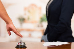 Closeup customer guest hand reaching for traditional reception bell with uniformed employee in background Stock Photography