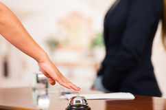 Closeup customer guest hand reaching for traditional reception bell with uniformed employee in background Stock Photo