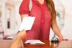 Closeup customer guest and hotel receptionist interacting at front desk, bell sitting on table, exchanging paper. Reservation Stock Photo