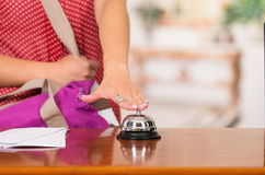 Closeup customer guest and hotel receptionist interacting at front desk, bell sitting on table, exchanging room key.  Stock Photography