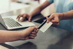Closeup Customer Paying with Credit Card in Store. Close up of Man giving Credit Card to Young Black Woman using Laptop in Store. Female Employee takes Payment Stock Image