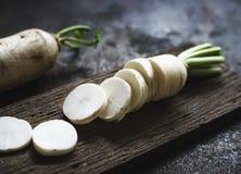 Closeup of cut daikon radish on wooden cutting-board Stock Photos
