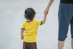 Closeup cute asian kid walk in the hand of parent on concrete floor textured background. Closeup cute kid walk in the hand of parent on concrete floor textured stock image