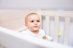 Closeup of a cute baby looking up in crib Stock Photo