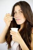Closeup of cute brunette eating yogurt Stock Photography