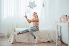 Closeup cute brunette girl in the studio, smiling broadly and playing with transparent and silver balloons. Royalty Free Stock Photo