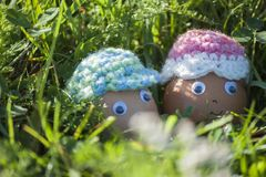 Closeup of cute couple of Easter eggs with smiling faces. In spring sunlight of green grass Stock Images