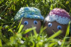 Closeup of cute couple of Easter eggs with smiling faces. In spring sunlight of green grass Stock Photo