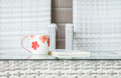 Closeup cute cup on blurred book and wood weave table and chair textured background Royalty Free Stock Photography