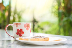 Closeup cute cup on blurred marble desk and garden view in the morning textured background Stock Images