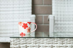 Closeup cute cup on blurred wood weave table and chair textured background Royalty Free Stock Photos