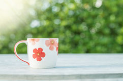 Closeup cute cup of coffee on blurred concrete desk and garden view in the morning textured background Stock Photo