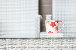 Closeup cute cup on white book on blurred wood weave table and chair textured background Stock Image