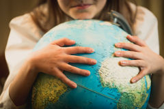 Closeup of cute girl holding hands on Earth globe. Concept of en Stock Image