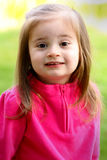 Little 2 year old girl. A closeup of a cute happy little girl in pink with long dark hair. Shallow depth of field Stock Images