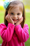 Sweet 2 year old with hair bows. A closeup of a cute happy little girl in pink with painted fingernails and bows in her long dark hair. Shallow depth of field stock photography